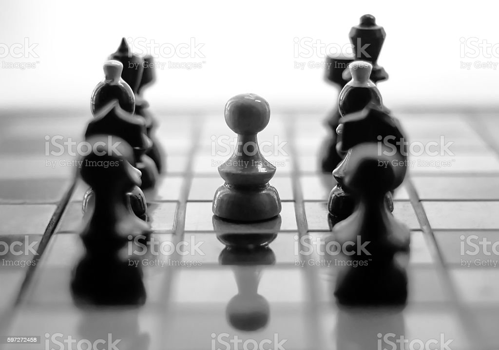 white pawn surrounded by black chess pieces royalty-free stock photo