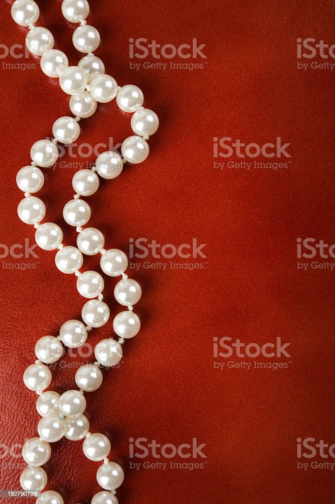 White pearl necklace on a red background stock photo