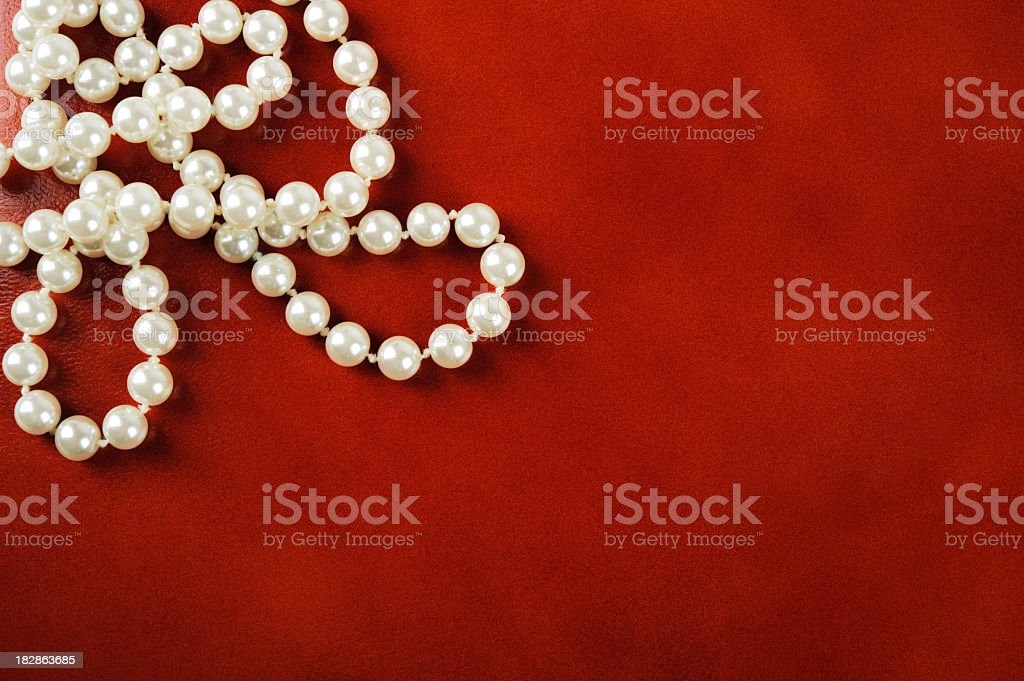 A white pearl necklace on a red background royalty-free stock photo
