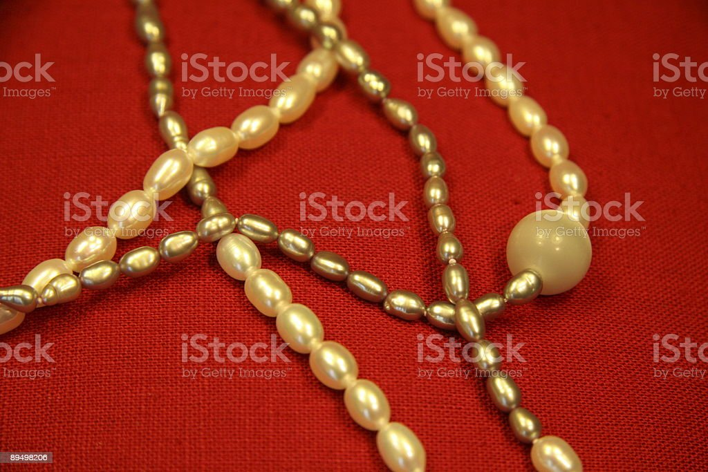 White pearl necklace on red background royalty free stockfoto