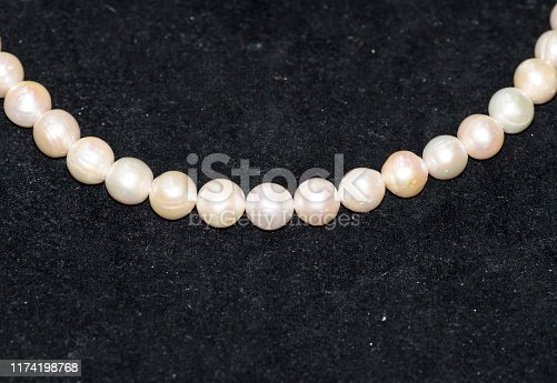868408882istockphoto White pearls on black background 1174198768