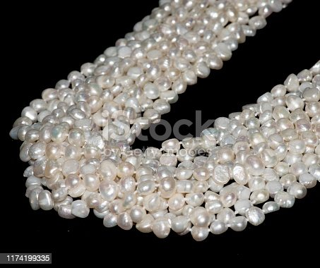 868408882istockphoto White pearls on black background 1174199335