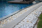 swimming pool drainage system grating covered with round white river stone pebble. swimming pool architectural detail design. White pebble contrasting with dark grey aggregate stone pool edge