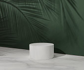 istock 3D White pedestal podium with palm tree leaf shadow over dark green natural background wall. Marble summer display showcase for beauty cosmetics products. Trendy Abstract studio 3d render illustration 1268320064