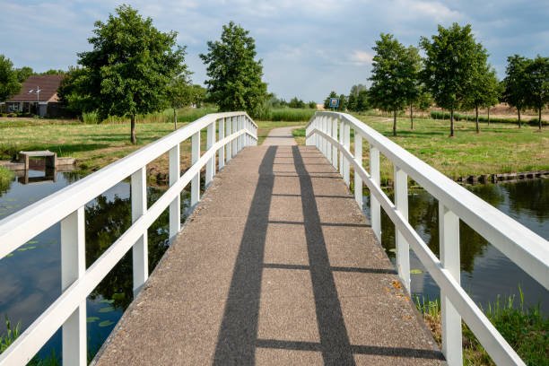 White pedestrians and bicycle bridge over a canal Traditional white wooden footbridge or cyclists bridge in a park or residential area. A Dutch landscape with bike path over water channels and walking areas footbridge stock pictures, royalty-free photos & images