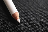 white pencil for french manicure on a black textured background