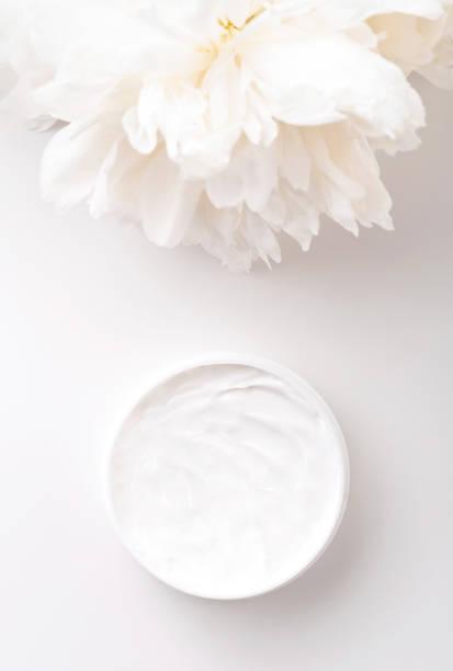 weiße pfingstrose und mockup gesicht und körpercreme auf weißem hintergrund. kosmetikkonzept. - pfingstrosen pflege stock-fotos und bilder