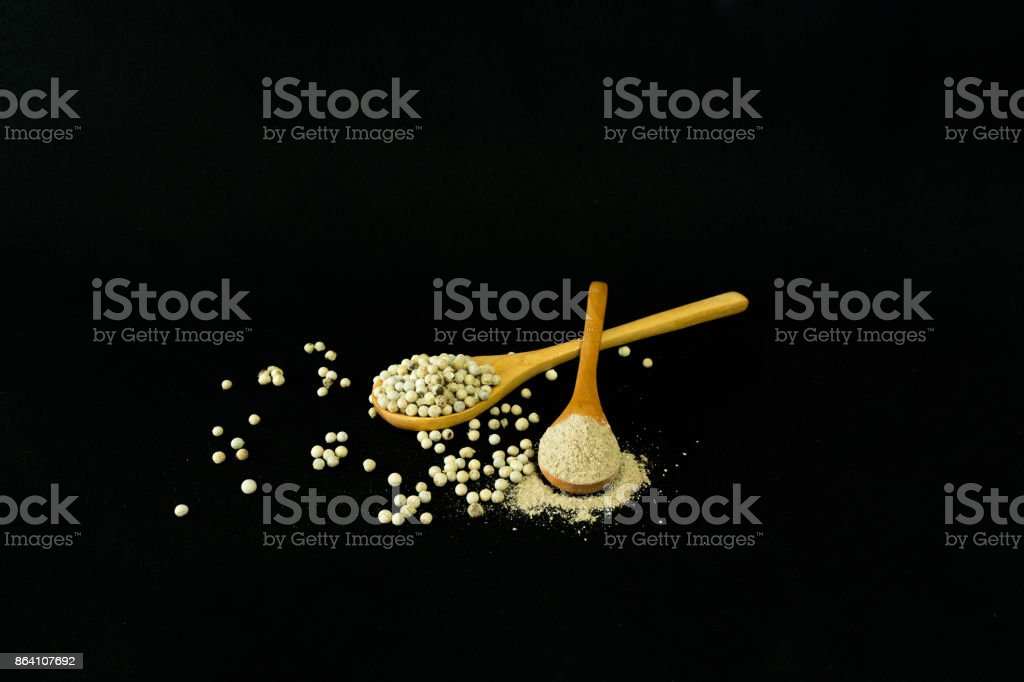 white peppercorn seed in wooden spoon on black background royalty-free stock photo