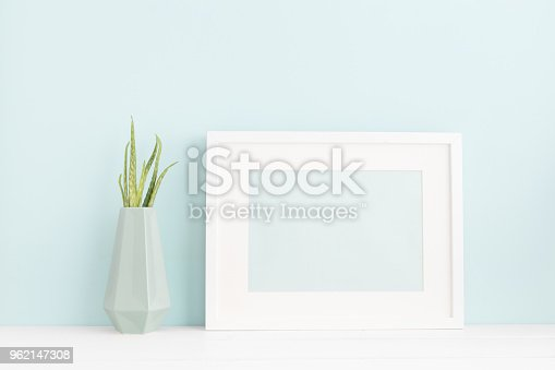 istock White photo frame and a plant on a pastel blue background mock up. 962147308