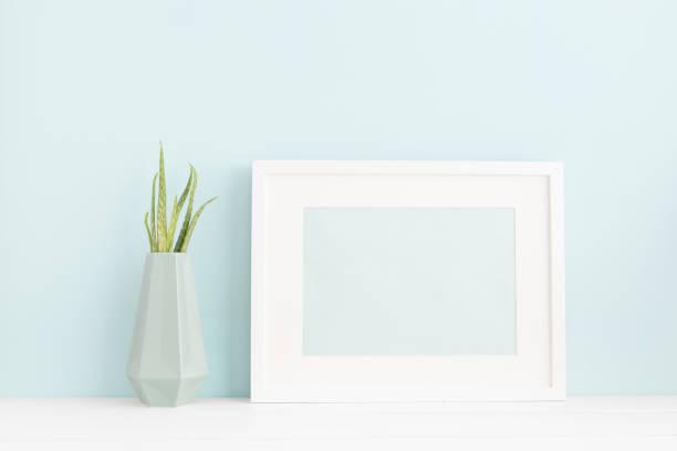 weißer bilderrahmen und eine anlage auf einem pastellblau hintergrund mock-up. - desktop foto stock-fotos und bilder