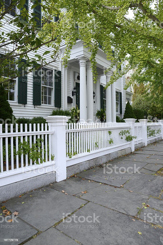 white picket fence by a typical federal style house stock photo