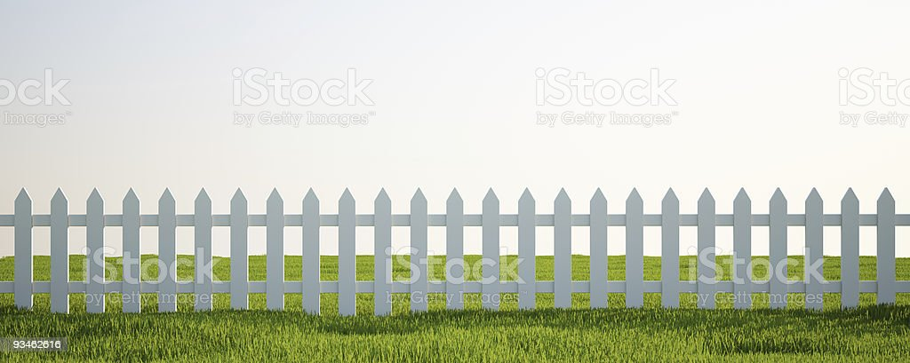 White picket fence on grass stock photo