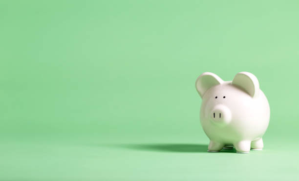 white piggy bank on a green background - piggy bank stock photos and pictures