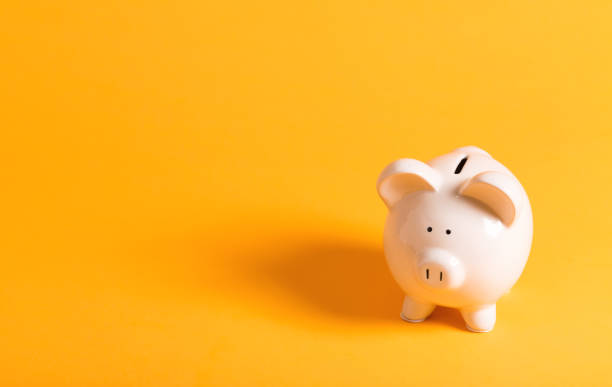 White piggy bank on yellow stock photo