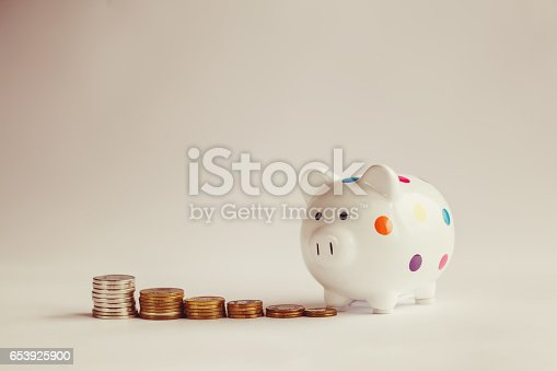 istock White piggy bank or money box with money coins. 653925900