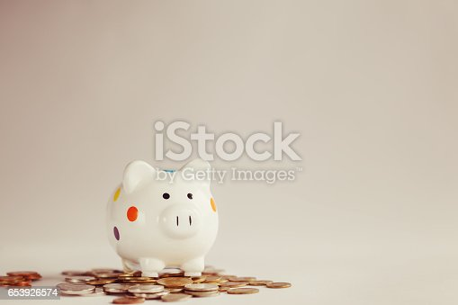 istock White piggy bank or money box with money coins 653926574