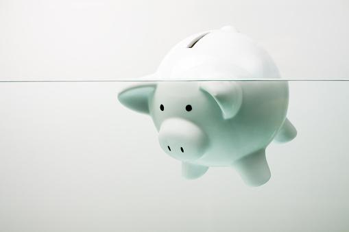 istock White piggy bank sinking in water 170619460