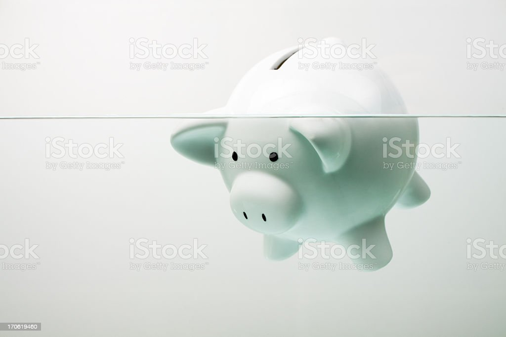 White piggy bank sinking in water stock photo
