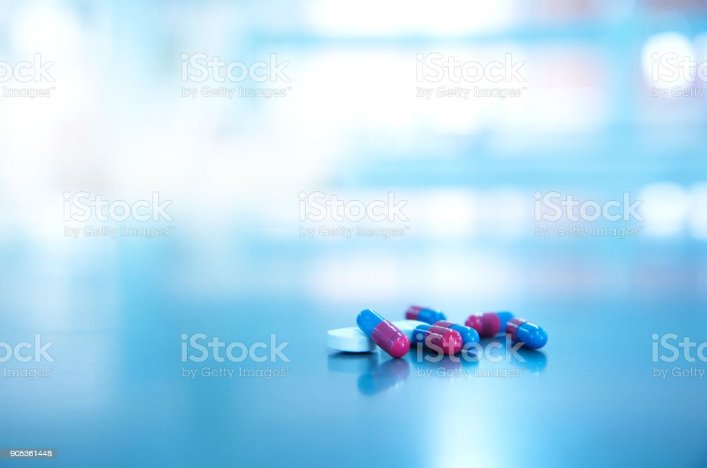 white pill and red blue capsule of medical health drug in light background stock photo