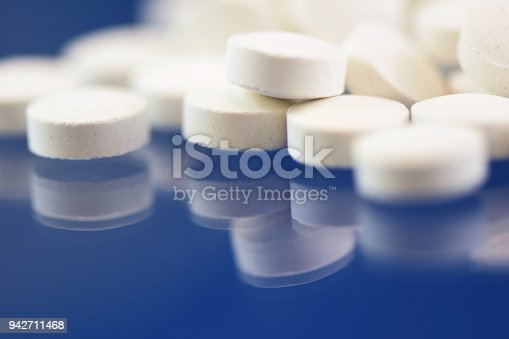 A small heap of white zinc tablets isolated on a dark blue background with a reflection.