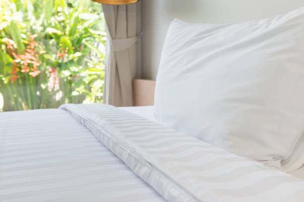 white pillow and white bed in bed room - indumento sportivo protettivo foto e immagini stock