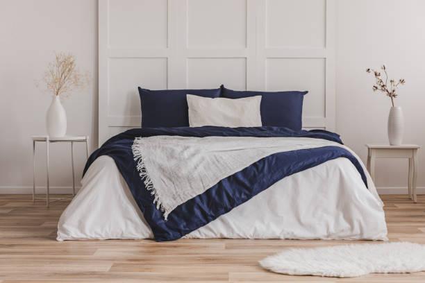 weißen kissen auf blauen bettwäsche auf king size-bett im modischen schlafzimmer innenraum - marineblau schlafzimmer stock-fotos und bilder