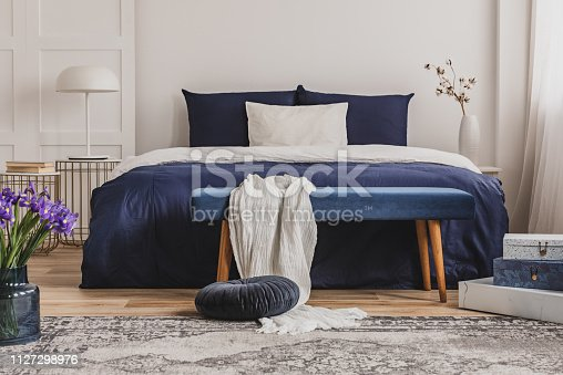 White pillow on blue bedding on king size bed in fashionable bedroom interior