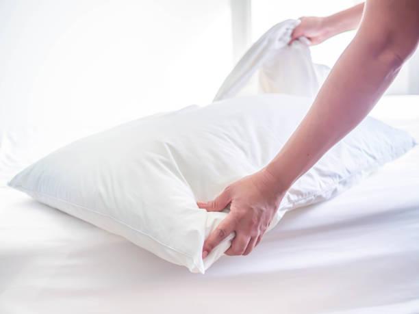 weißes kissen auf dem bett im schlafzimmer mit frau hand, die das zimmer machen. - verwandlungskissen stock-fotos und bilder