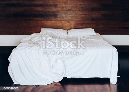 white pillows on bed sheet and blanket with wrinkle messy in the bedroom.