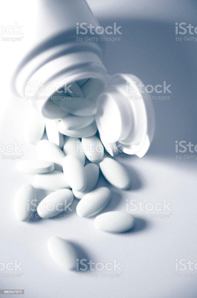 Comprimidos brancos, saindo de um frasco caído - foto de acervo