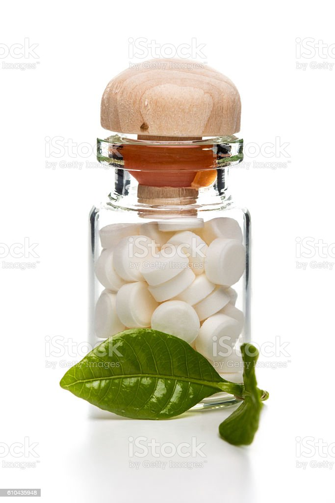 White pills in glass container with wooden top stock photo