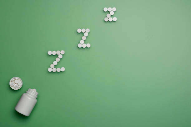 white pills in z shape. soporific pills on green background - sleeping pill stock photos and pictures
