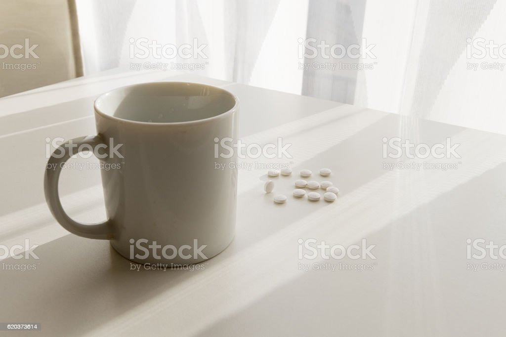 white pills lying next to a glass of water on foto de stock royalty-free