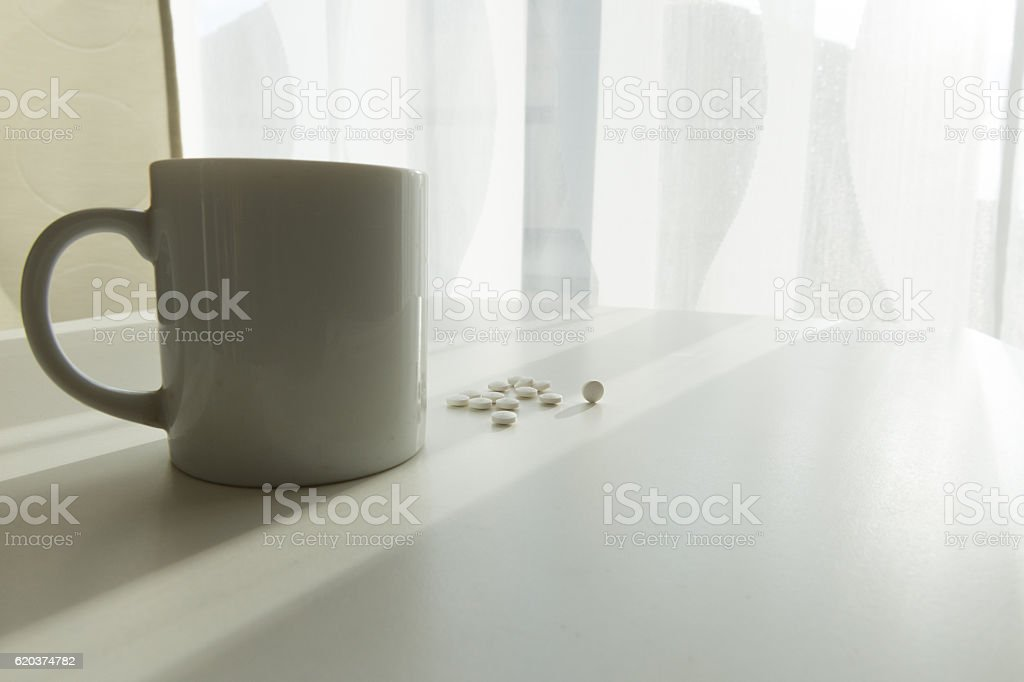 white pills lying next to a glass of water on zbiór zdjęć royalty-free