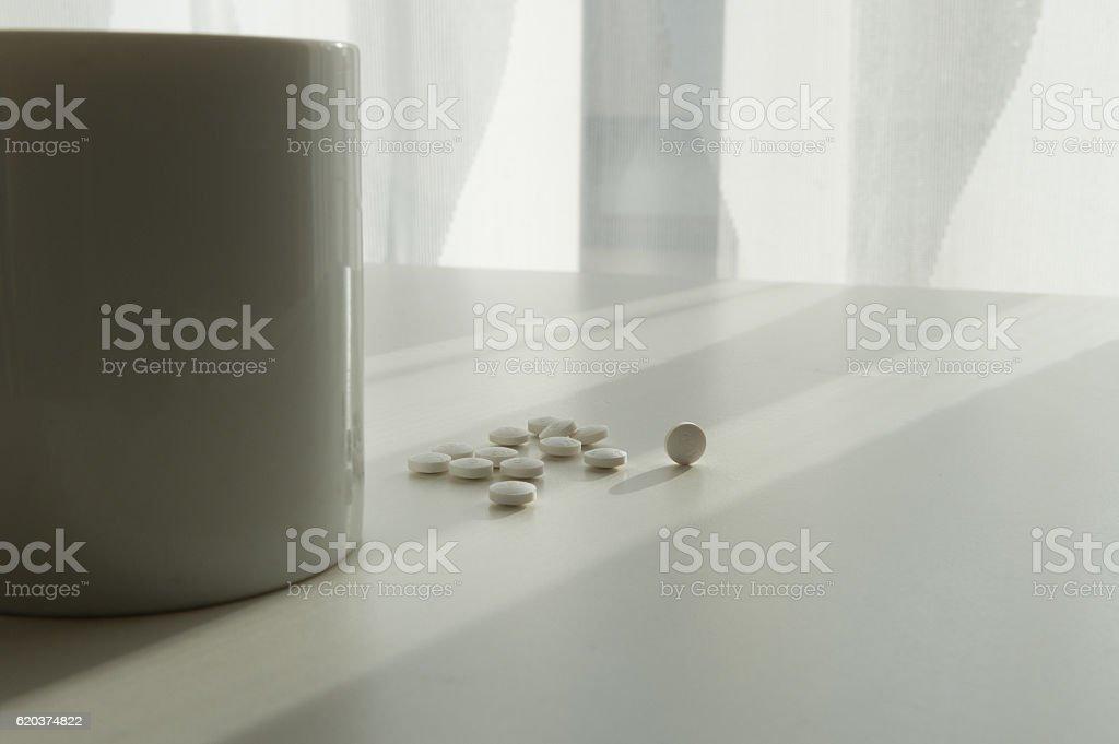 white pills lying next to a glass of water on zbiór zdjęć royalty-free