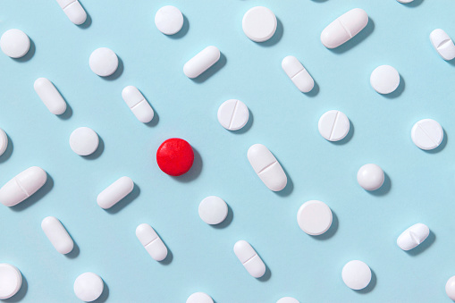 White pills arrangement on soft blue background with one red pill standing out from them
