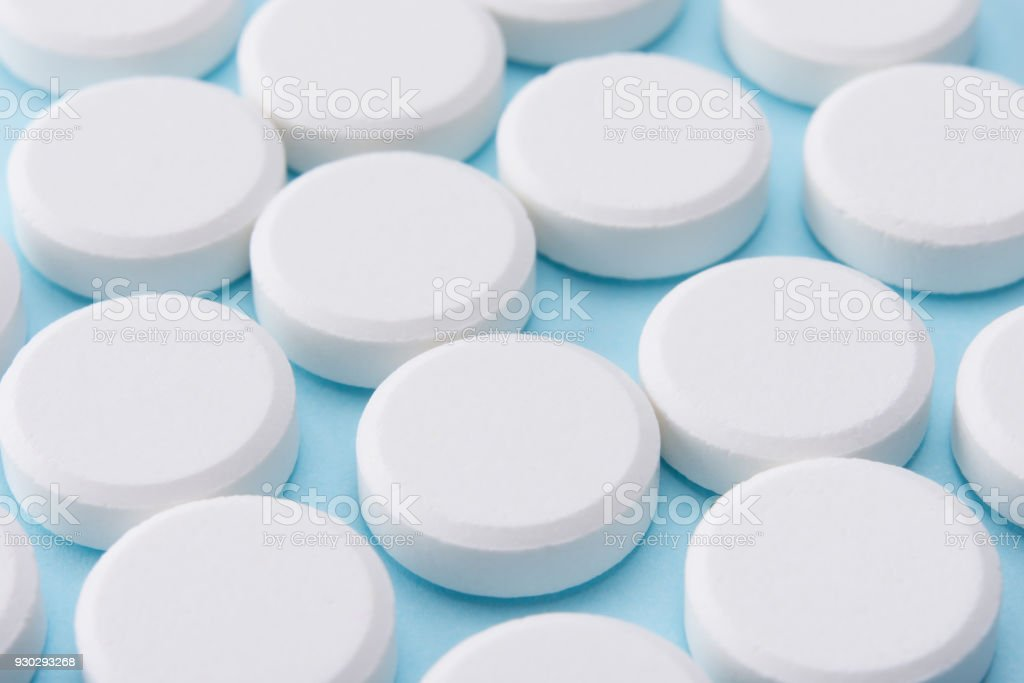 white pills on blue background stock photo