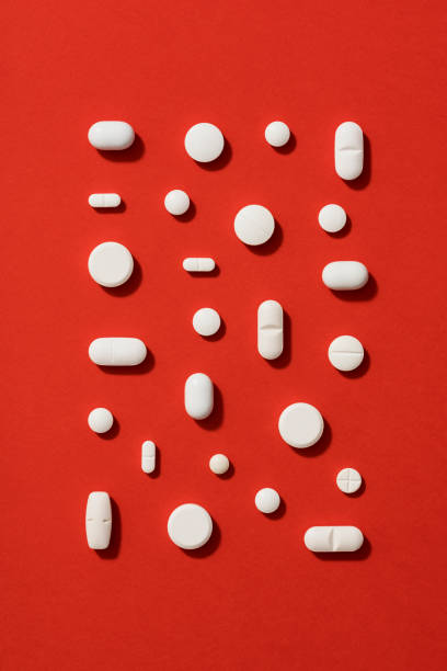 White pills on red background stock photo