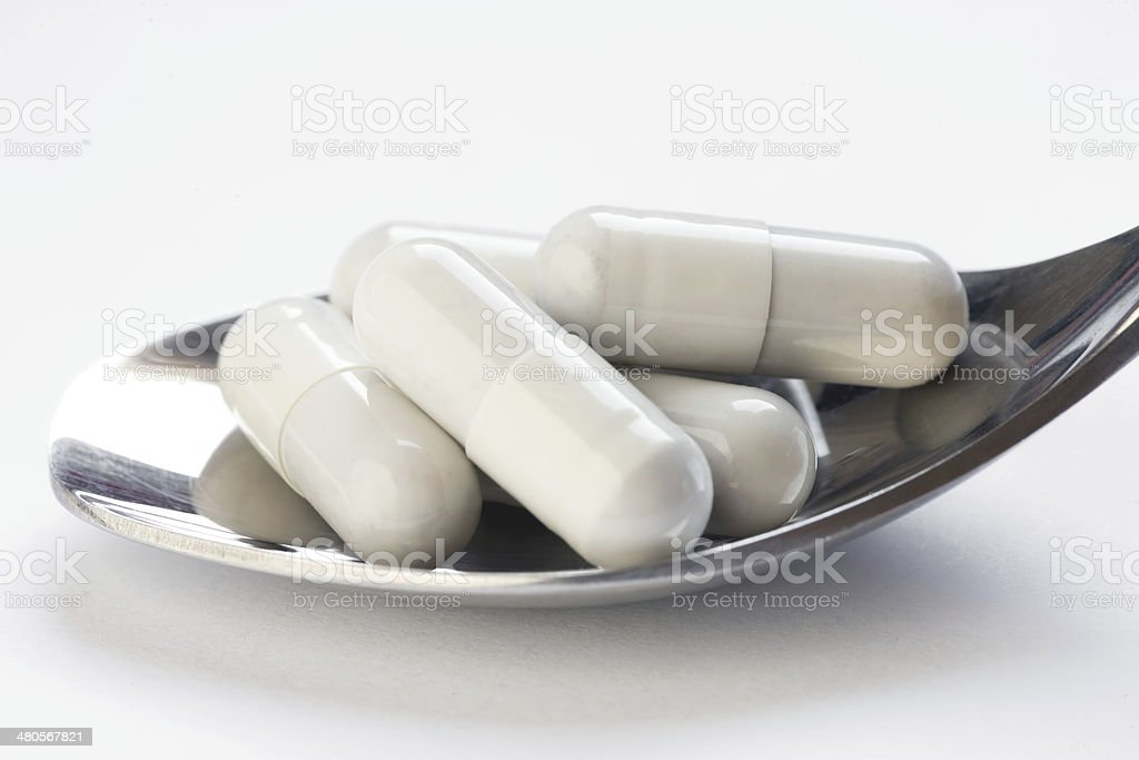White Pills on spoon - Close-up royalty-free stock photo