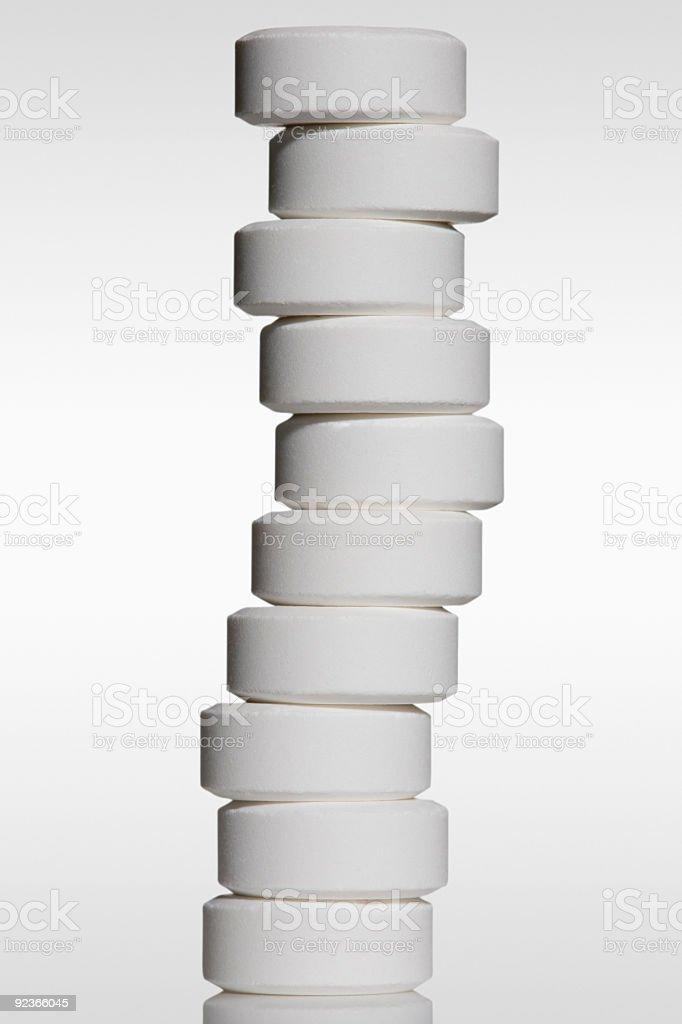 White pills stacked on white background royalty-free stock photo
