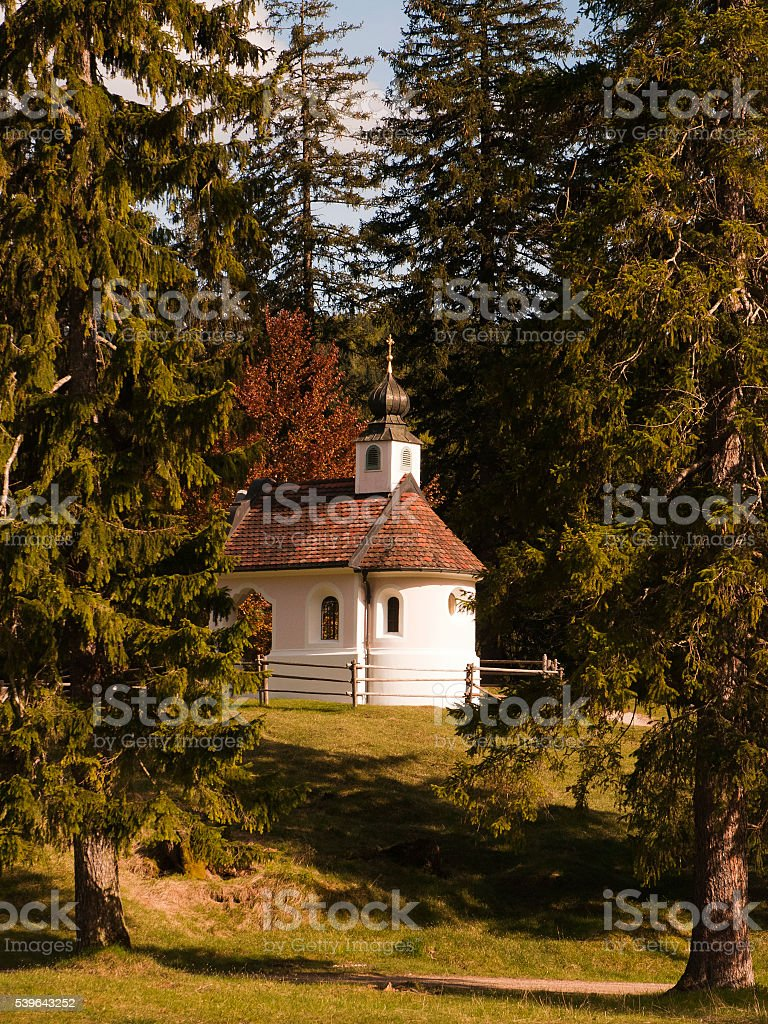 White pink chapel behind trees near Mittenwald in Bavaria stock photo