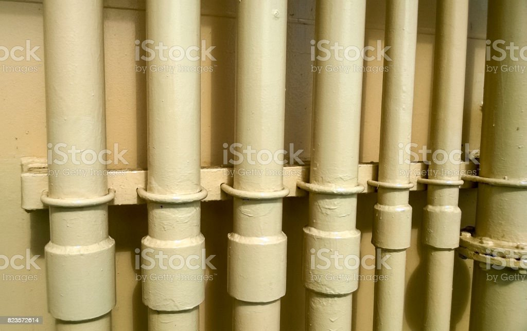 White pipes near the wall. Flanged connection on a gray pipe. Pipes on the deck of the ship stock photo