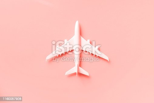 istock White plane, airplane on trendy coral color background with copy space. Top view, flat lay. Minimal style design. Travel, vacation concept. Banner. 1160057928