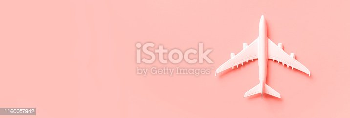 istock White plane, airplane on trendy coral color background with copy space. Top view, flat lay. Minimal style design. Travel, vacation concept. Banner. 1160057942