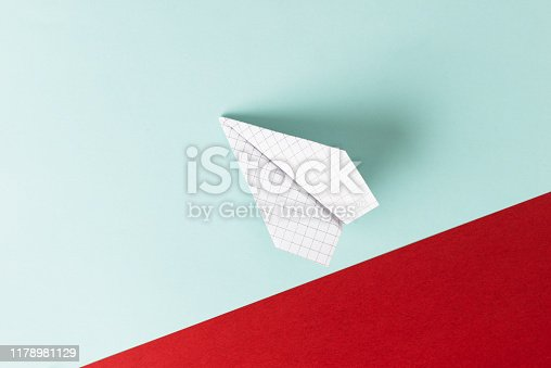 White paper plane is flying on blue background with red diagonal part representing lawn area.