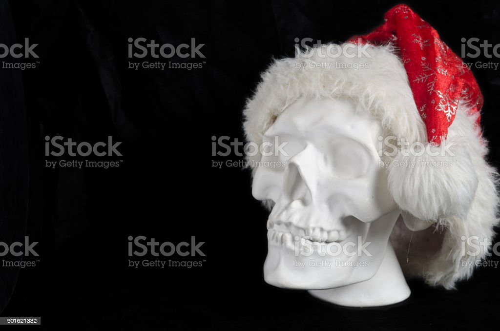 white plaster human skull on a black background in the Santa Claus hat stock photo