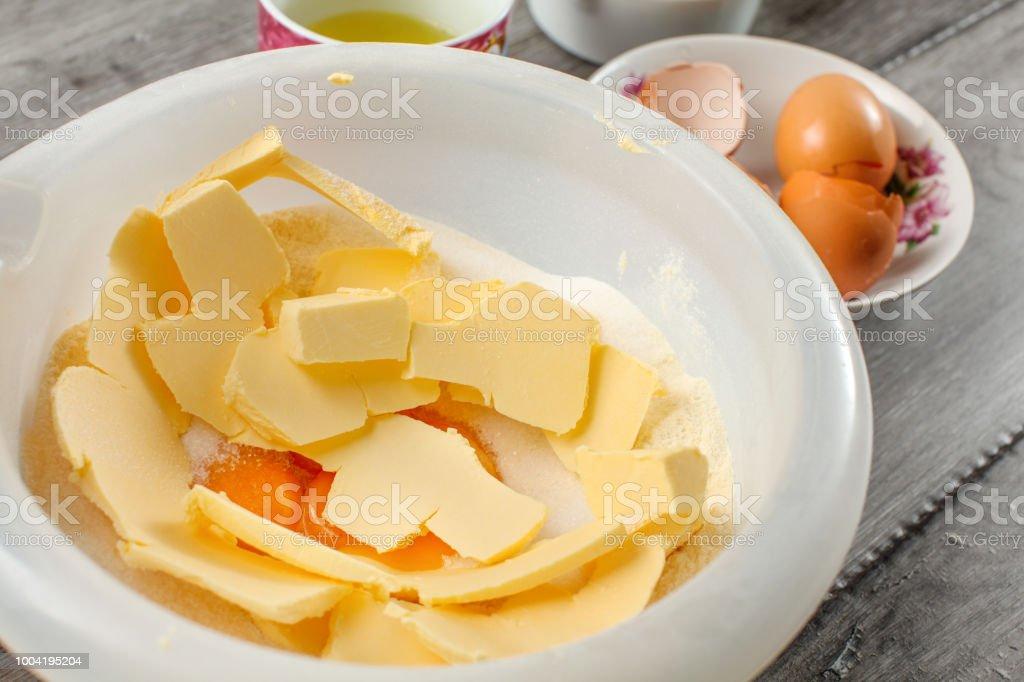Bacia de plástico branca com manteiga, gemas de ovo e açúcar misturado - preparação para assar um bolo. - foto de acervo