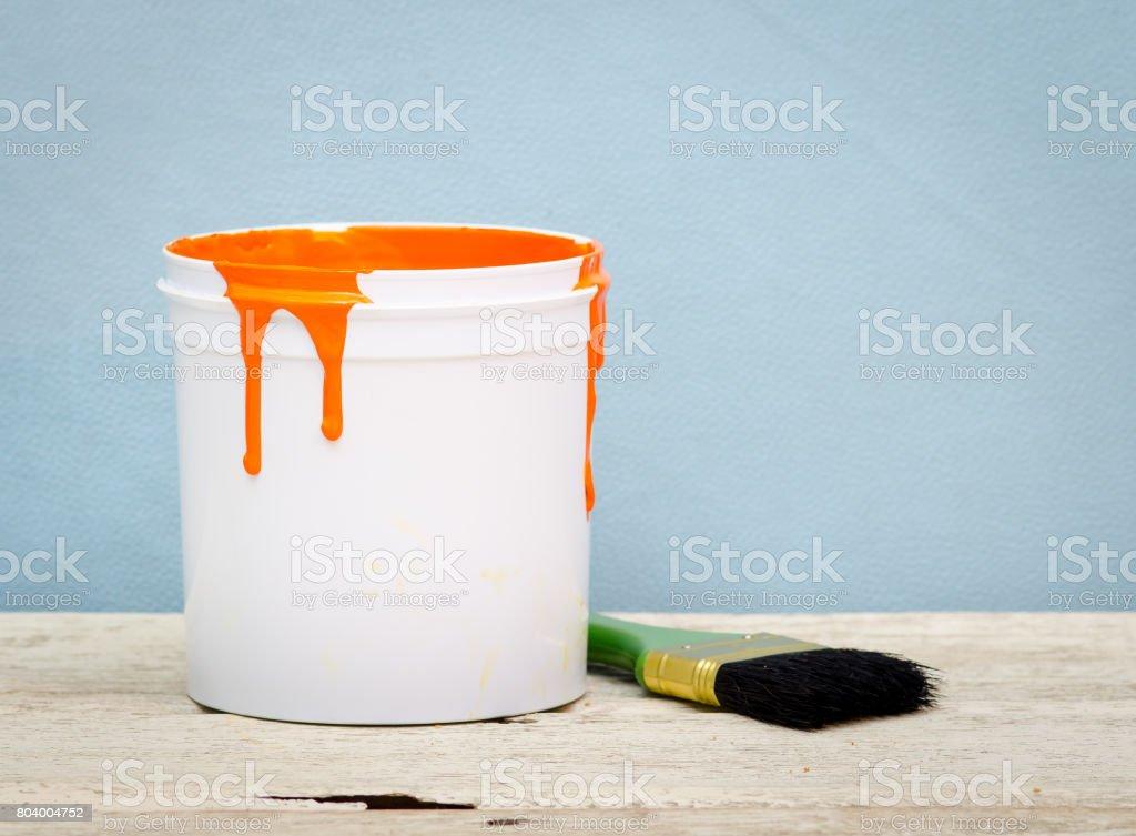 Balde de plástico branco com tinta de cor laranja e escova em fundo de madeira, vintage - foto de acervo