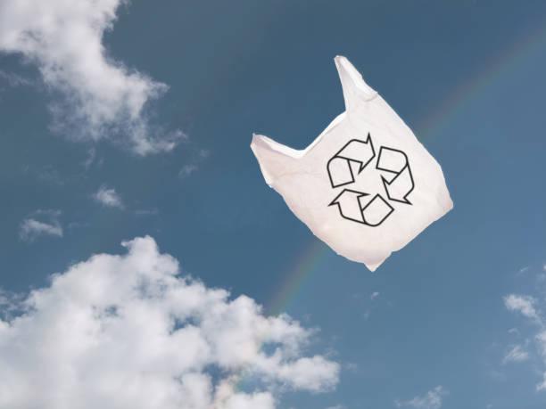weißen plastiktüte über himmel und regenbogen, im wind wehen. - windbeutel stock-fotos und bilder