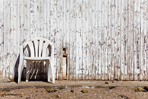 White plastic chair in front of grunge, weathered, wooden wall.